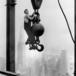 29 Sep 1930, Manhattan, New York City, New York State, USA --- A steel worker hangs stories above the streets of Manhattan while holding onto the end of a crane hook at the construction site of the Empire State Building. The Chrysler Building is viewable in the distance. --- Image by © Bettmann/CORBIS